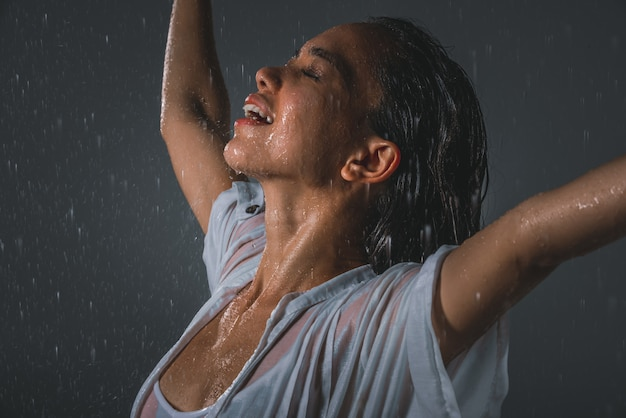 Woman feeling good and free under the summer rain