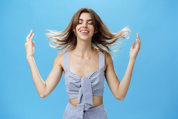 Женщина чувствует, как волосы наполняются силой после мытья их новым шампунем или косметическим продуктом, играя с прической, закрывая глаза с восхищенной счастливой улыбкой, стоя нежно и чувственно над синей стеной