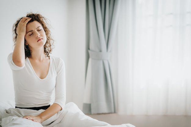 Woman feeling headache after wake up in the morning