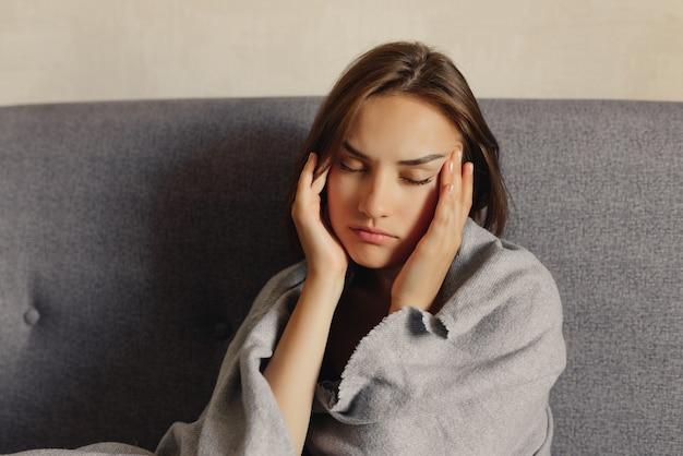 頭痛を感じ、目を閉じ、寺院に手をつないで、気分が悪くなった女性。健康問題のコンセプトです。
