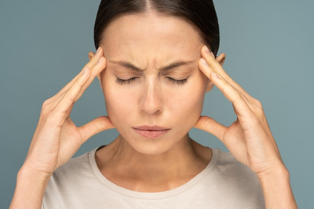 Woman feeling headache, weakness, massaging temples, tired, exhausted from overwork, isolated