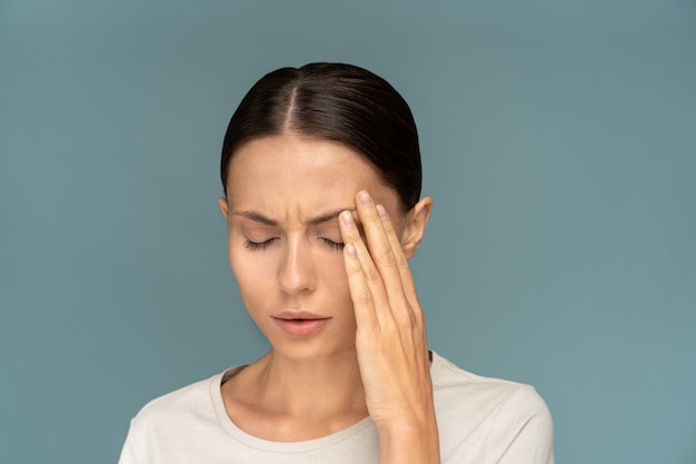 Woman feeling headache, weakness, massaging temples, tired, exhausted