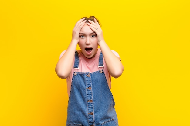 Woman feeling horrified and shocked, raising hands to head and panicking at a mistake