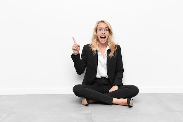 Woman feeling like a happy and excited genius after realizing an idea, cheerfully raising finger, eureka!