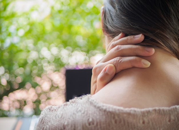 Woman feeling neck pain after long hours work on computer. office syndrome concept.