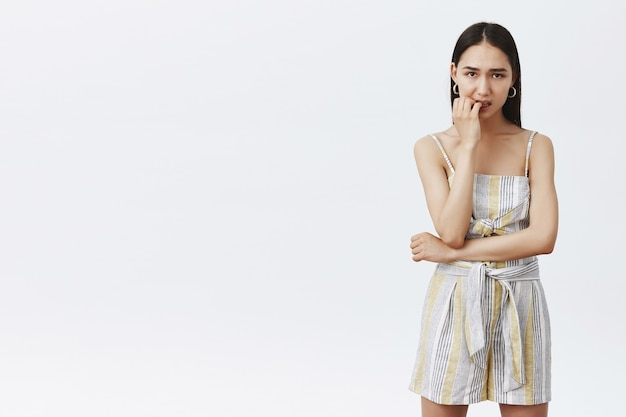 Woman feeling nervous waiting for results of competition, dreaming of first place. portrait of anxious intense good-looking female in summer outfit, biting fingernails and staring worried