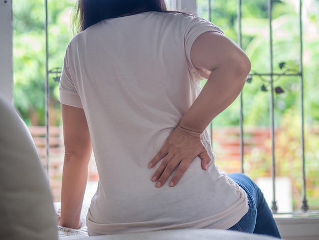 Woman feeling pain in her back sitting on the sofa at home