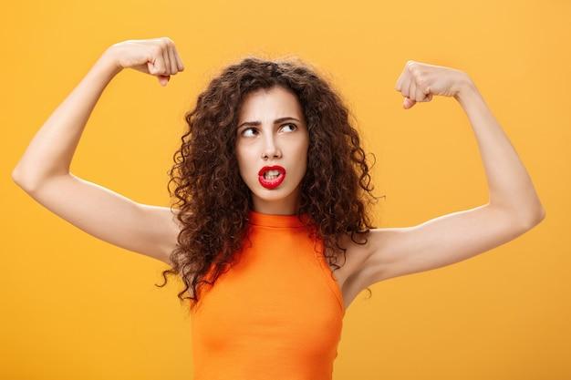 オレンジ色の背景の上にポーズをとって右上隅を見て筋肉と上腕二頭筋を見せているジムで激しい顔をしているくいしばられた握りこぶしで力強くて強い挙手を感じている女性。