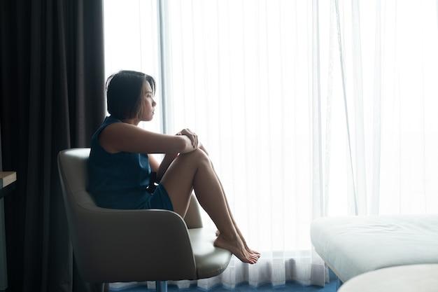 窓際で悲しみを感じる女性、孤独、傷ついた心、不幸な女性、気分が悪くなる、悲しい女の子、女の子が悲しい