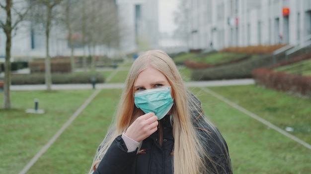 Женщина чувствует себя спасенной, надевая на лицо медицинскую маску