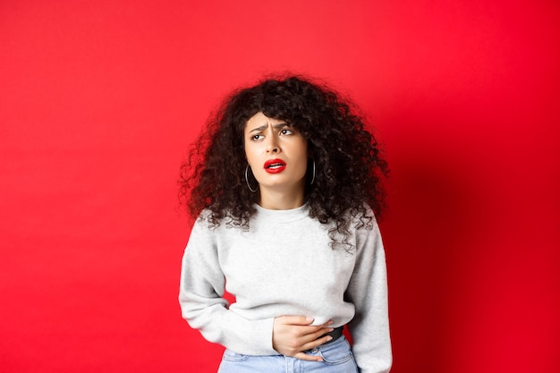 Woman feeling sick, bending and touching belly, having stomach ache or menstrual cramps, standing on red background.