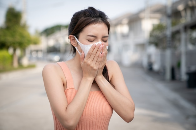 Woman feeling sick, coughing or sneezing. she wearing protective mask.