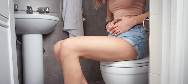 Женщина чувствует боль в животе, сидя в туалетной комнате.