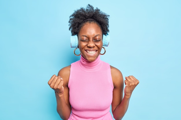 Woman feels joy of victory shakes fists gestures actively celebrates success clenches teeth listens music via wireless headphones isolated on blue