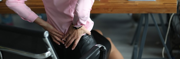 Woman feels painful back pain sitting workplace spine problems stress concept
