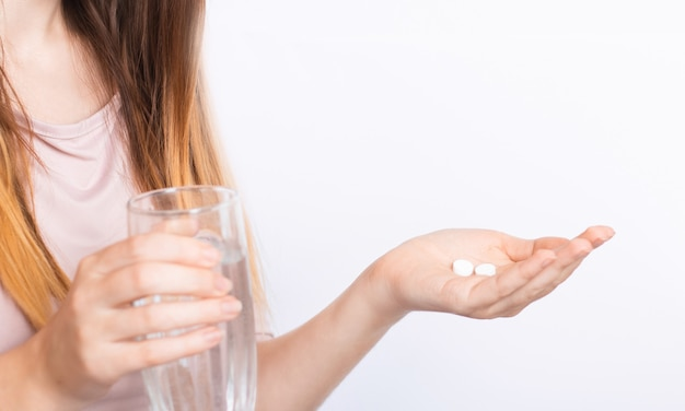 Woman feels sick, holds pills and a glass of water in detail on white
