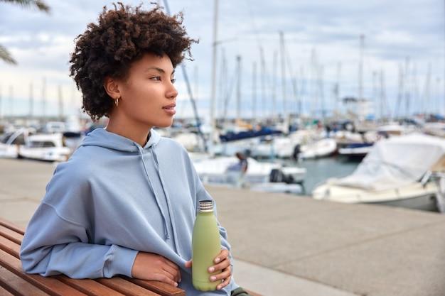 女性は喉が渇いたと感じて水のボトルを保持します港で美しい海の景色のポーズを賞賛します物思いにふける表情は屋外で自由な時間を過ごします