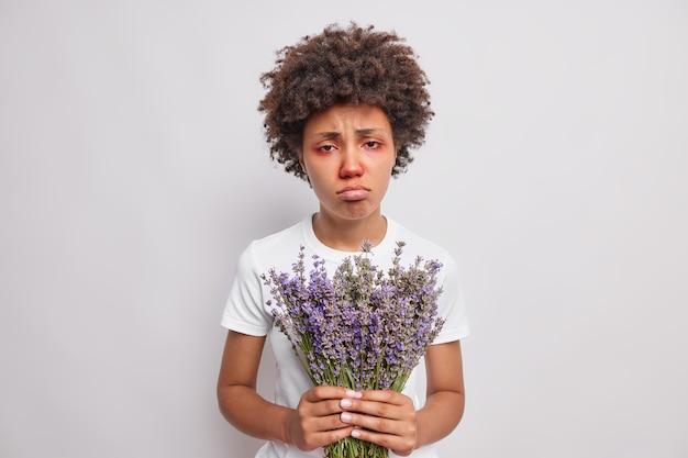 La donna non si sente bene tiene la lavanda ha una reazione allergica al polline rosso prurito occhi infiammati naso che cola borse labbra indossa maglietta casual isolato su bianco