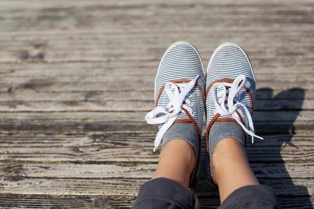 나무 부두 배경에 캐주얼 신발에 여자 발