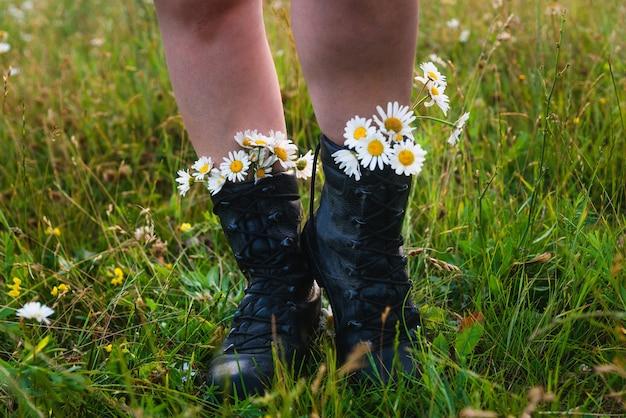 여름날 푸른 잔디에 데이지 꽃이 달린 하이킹 부츠를 신은 여자 발