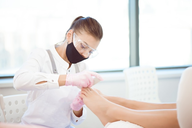 Woman feet receiving pedicure. close up concept.