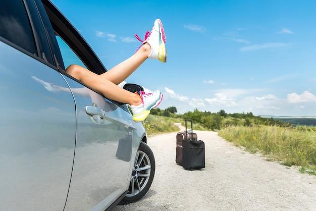 여자 발이 편안 하 고 차 창에서 떨어져 있습니다. 휴가 및 자유 개념
