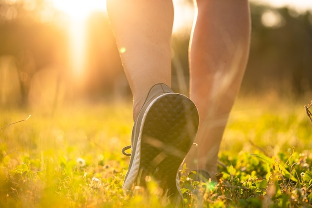 Woman feet in sneakers outdoors close up, training on a sunset in a park with green grass, beautiful sporty legs