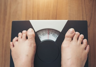 Woman feet standing on Weight Scale on wooden background