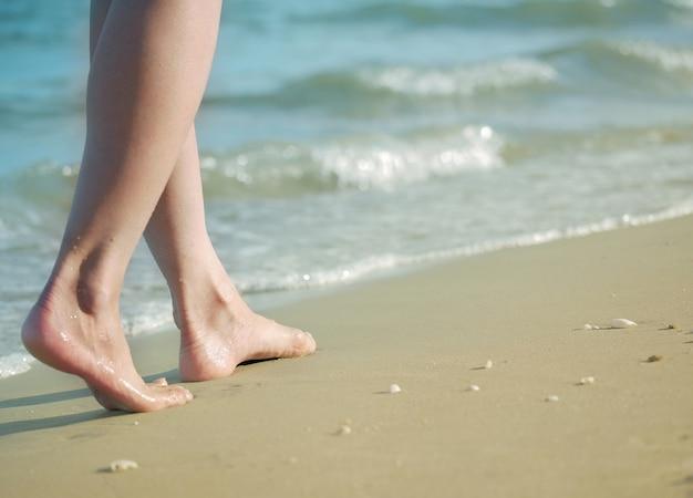 Woman feet walking barefoot on sandy beach of sea.