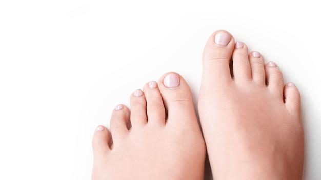Ноги женщины с мягким розовым маникюром, изолированные на белом фоне