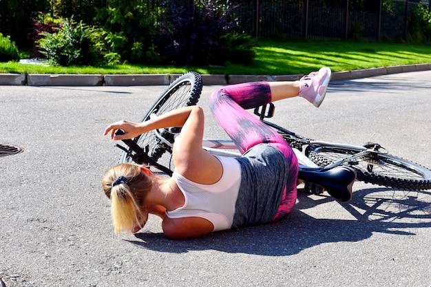 女性が道路で自転車から落ちた