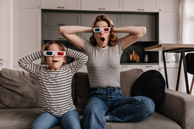 Woman and female child are shocked watching movie in 3d, sitting on sofa in apartment.