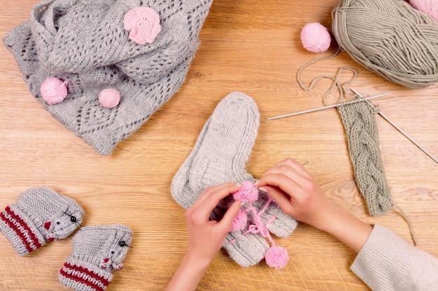 女性女性女の子は新しい暖かいソックスを編む。仕立て屋の職場。上面図
