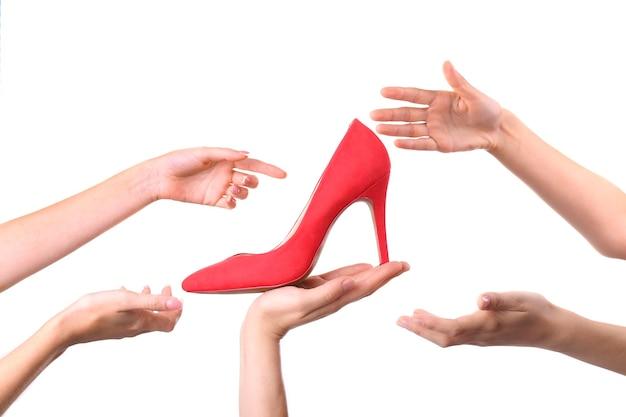 Женщина в женских руках держит обувь для продажи, изолированные на белом фоне