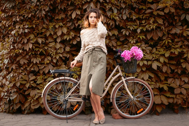 Woman in feminine clothes poses on bicycle in a summer day