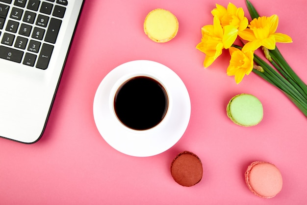 Woman or feminine workspace with notebook, coffee, macarons and flowers