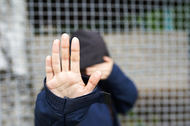 Woman behind the fence, close-up of a refugee woman's hand