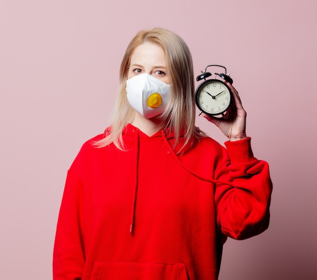 Woman in ffp2 anti-dust standart face mask hold alarm clock on pink background