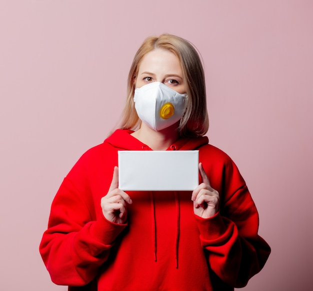 Woman in ffp2 anti-dust standart face mask hold banner on pink background