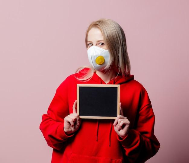 Woman in ffp2 anti-dust standart face mask hold blackboard on pink background