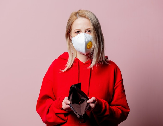 Woman in ffp2 anti-dust standart face mask hold empty wallet on pink background