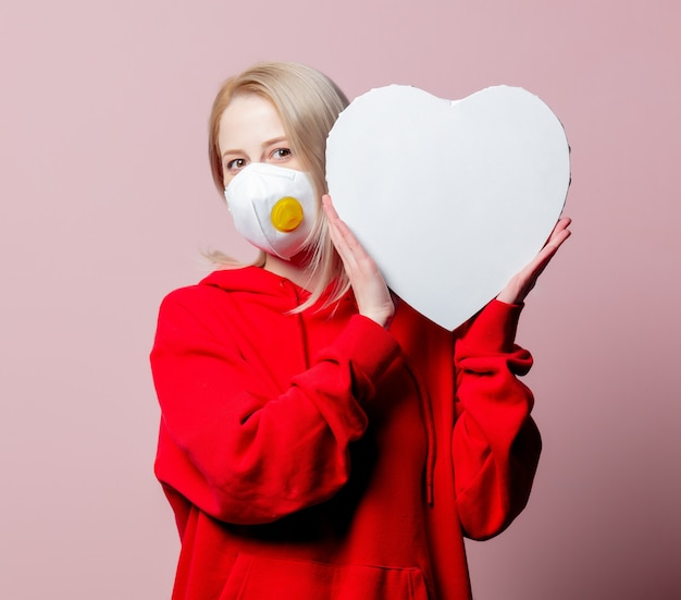 Woman in ffp2 anti-dust standart face mask hold heart shape banner on pink background