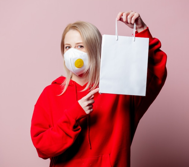 Woman in ffp2 anti-dust standart face mask hold shopping bag on pink background