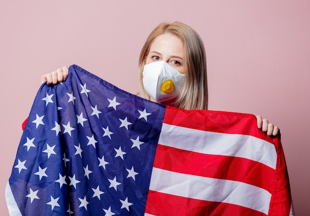 Woman in ffp2 anti-dust standart face mask hold usa flag on pink background