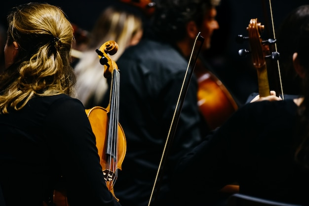 Woman fiddler during a concert, background in black.