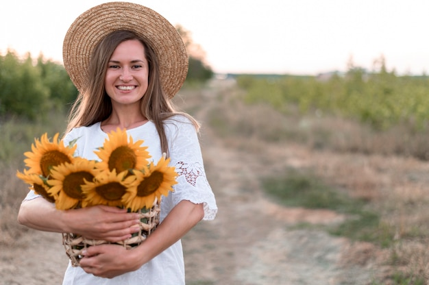 Woman in field holding sunflowers front view
