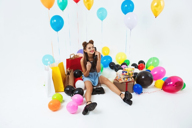 Woman fielding birthday calls, stting with big balloons and presents