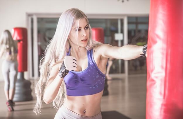 女性の戦闘機が重いボクシングバッグをヒット