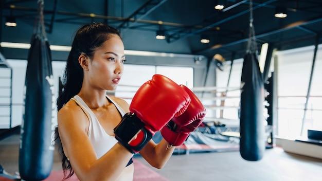 Combattente donna pratica boxe in palestra fitness class