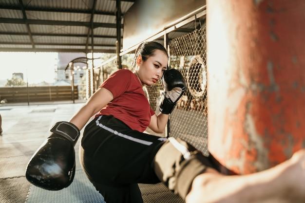 복싱 캠프에서 샌드백으로 몇 가지 차기를 연습하는 여자 전투기